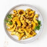 A bowl filled with delicata squash garnished with parsley.