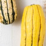 Whole delicata squash showing the varieties of colors.