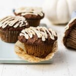 Muffins sitting on a blue cutting board next to a white pumpkin.