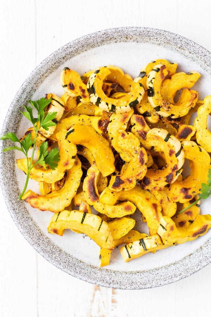 A plate with lots of roasted delicata squash.