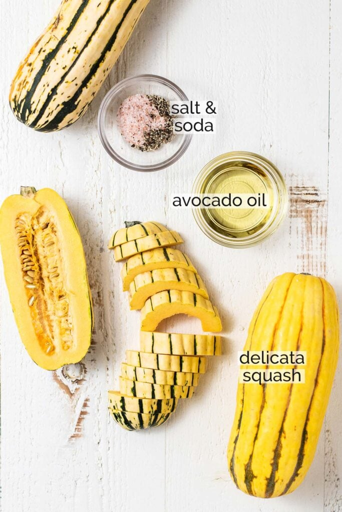 The ingredients for delicata squash including avocado oil, salt and pepper, and sliced delicata squash.
