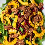 A white platter with a spinach salad topped with delicata squash, pomegranate, and pecans.