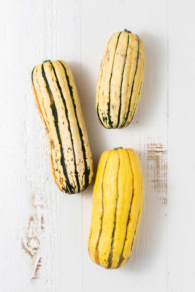 3 delicata squash shown whole.