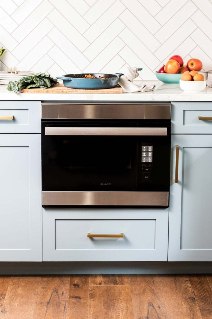 The Sharp SuperSteam+ Built-in Wall Oven shown with a skillet and a bowl of apples on the counter above it.