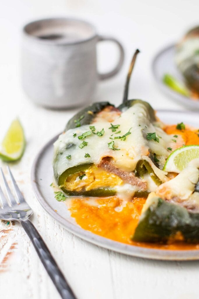 A close up look at a breakfast chile relleno stuffed with eggs, cheese, and sausage.