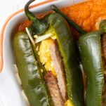 A close up look at a pepper sliced open and stuffed with eggs, cheese, and sausage.