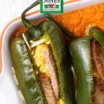 Chiles stuffed with sausage and egg siting in a casserole dish with a red relleno sauce.