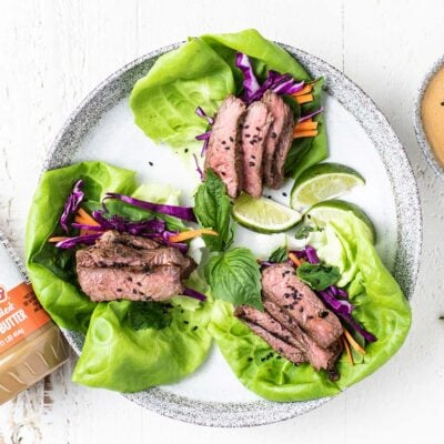 Leaves of lettuce filled with colorful veggies and thinly sliced steak.