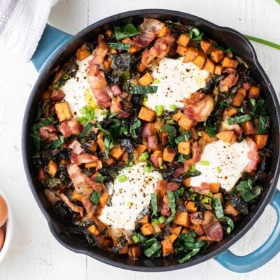 A sweet potato breakfast skillet baked with 4 eggs on top, shown next to a bowl of whole eggs.
