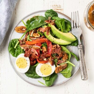 A beautiful salad topped with eggs, avocado, and roasted red peppers, topped with a hot bacon dressing.
