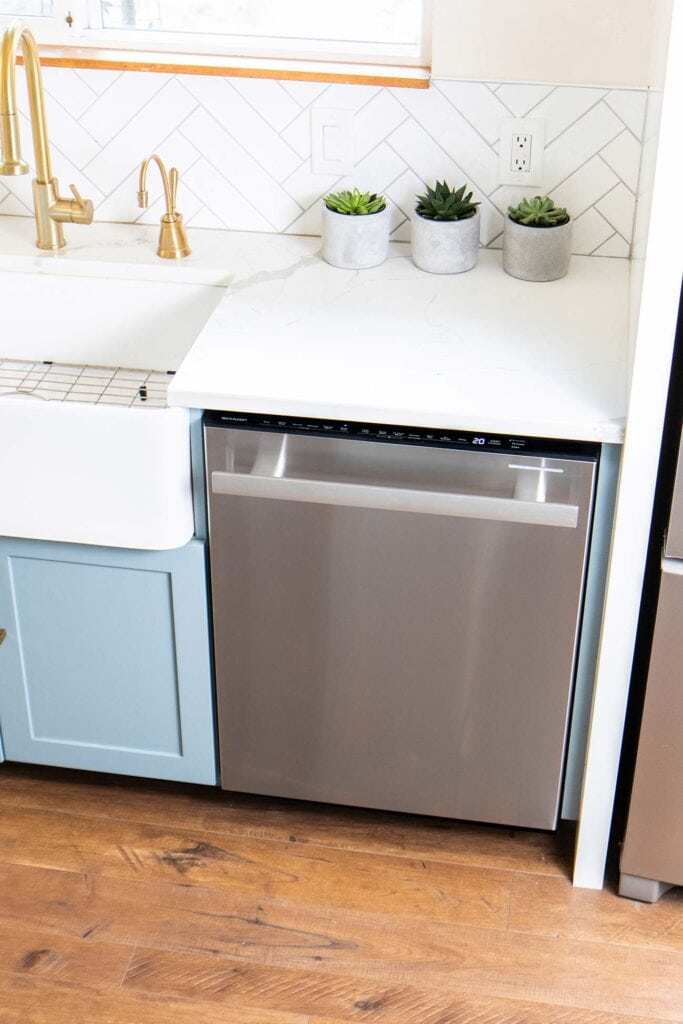 A view of a dishwasher installed next to a white farmhouse sink.