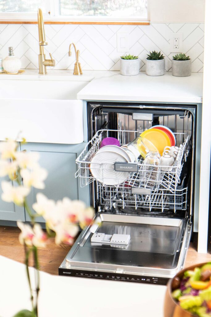 A dishwasher opened to show a half load of dishes.
