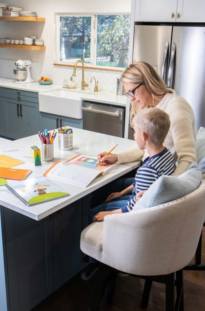MOm and son sitting together doing homework in a kitchen.