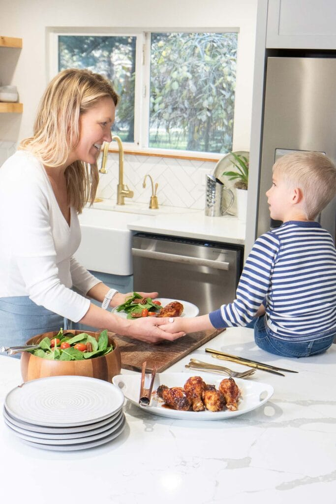 A mother and son serving dinner on a kitchen island.