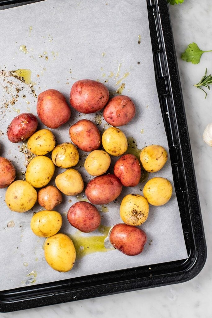 A baking pan with red and white potatoes prepared to bake.