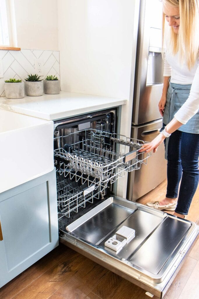 A woman pulling the top rack of an empty dishwasher out of an open machine.