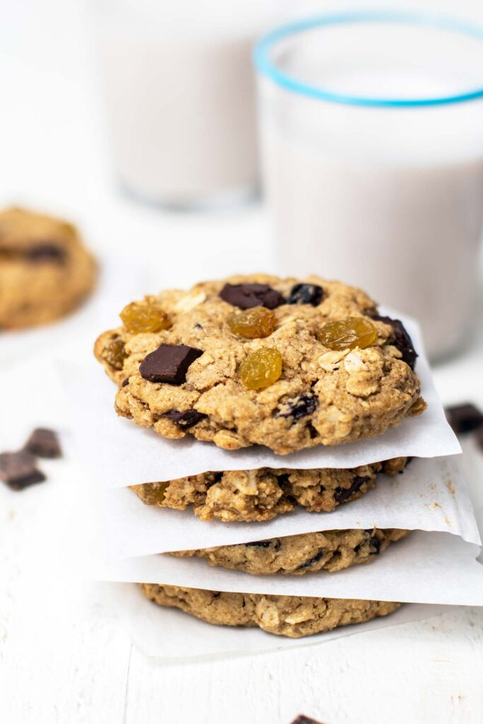 A stack of 4 gluten free oatmeal raisin cookies in front of a glass of milk.