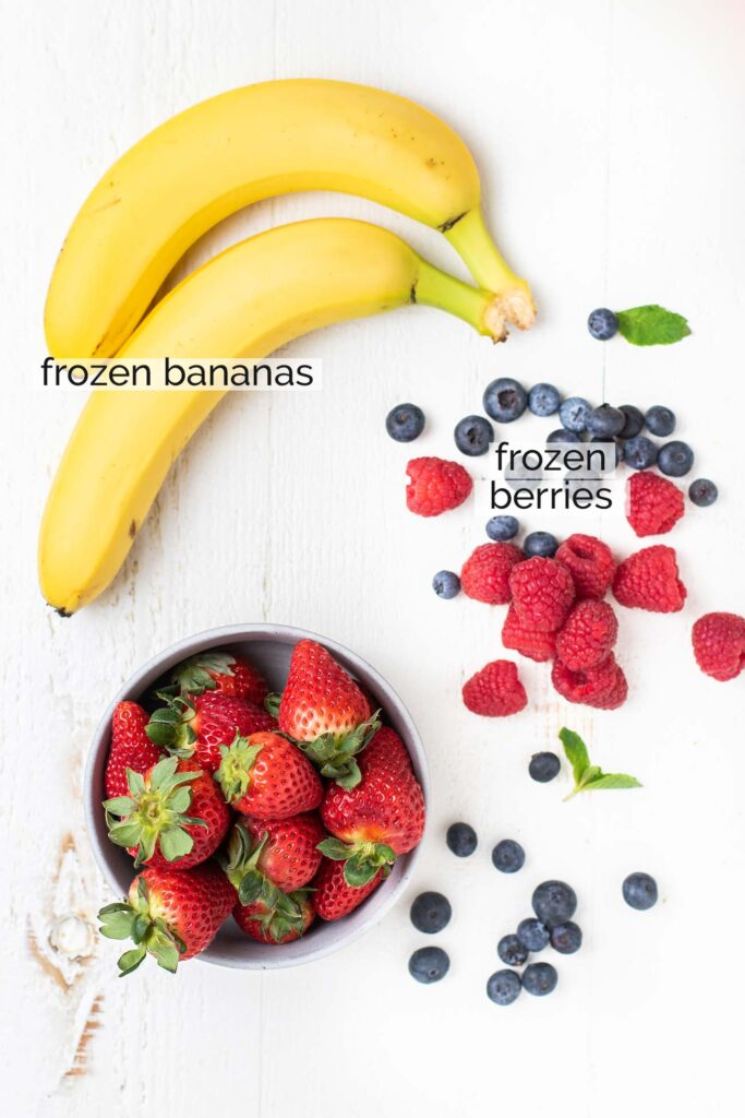 Bananas, strawberries, blueberries, and raspberries shown as fruit used in a banana berry smoothie bowl.