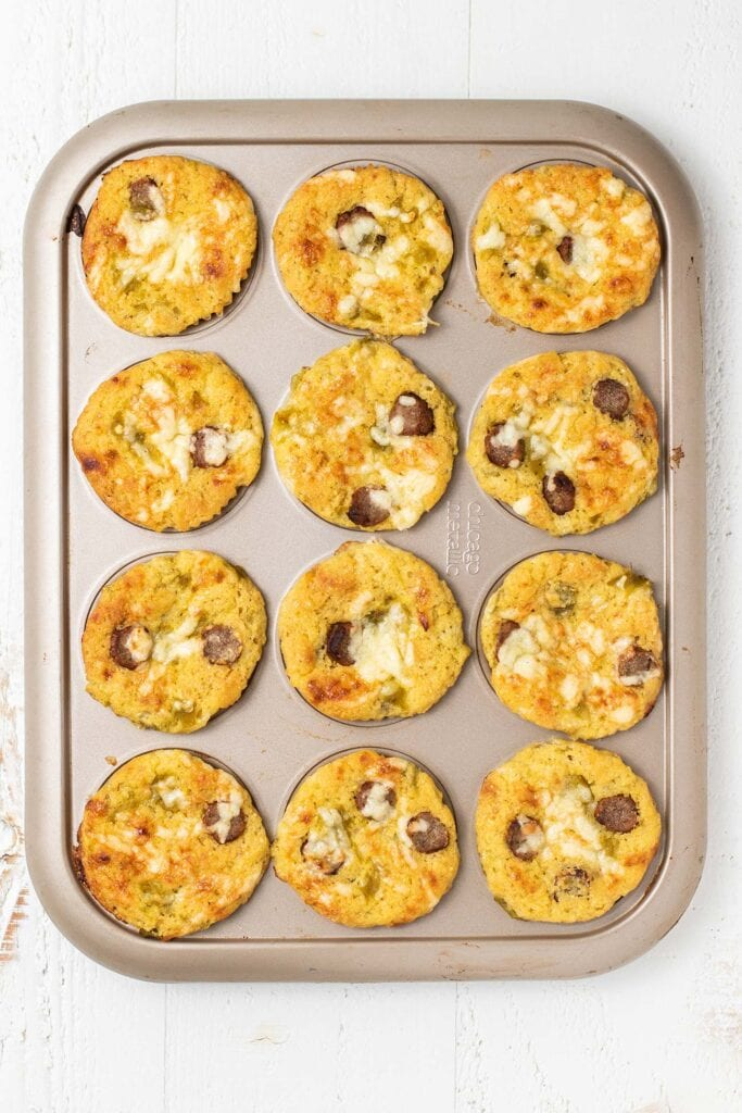 Baked gluten free cornbread muffins with sausage, cheese, and green chilis.