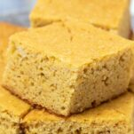 A close up at cornbread cut into large squares and arranged on a platter.