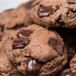 A plate with a stack of double chocolate chip cookies shown with melty chocolate chunks.