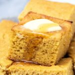 Cornbread slices stacked up, and with butter and honey dripping off the top.