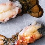 Raw lobster tails shown butterflied and brushed with a seasoned butter.