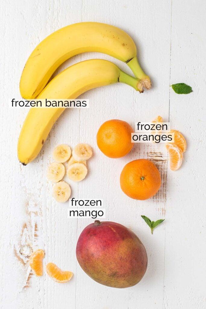Bananas, mandarin oranges, and mango shown ready to make smoothie bowls.