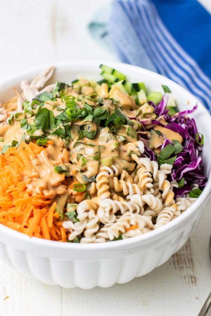 A colorful chicken pasta salad shown coated in a creamy nutty Thai dressing.