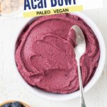 A bright purple thick smoothie in a bowl with topping suggestions in little bowls around it.