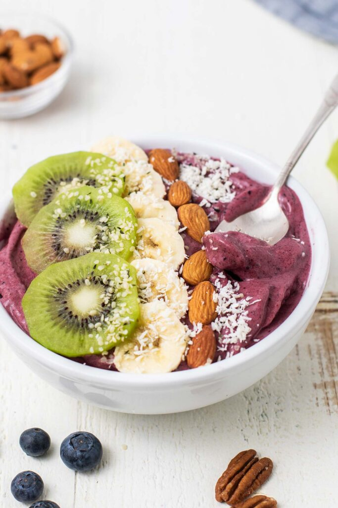 A side view of a thick acai smoothie bowl with lots of healthy toppings.