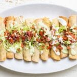 A white plate with a row of taquitos, garnished with salsa and avocado crema.