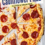 A baked cauliflower pizza topped with pepperoni, cut into slices.