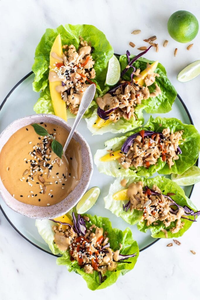 A plate of lettuce wraps surrounding a bowl of Thai almond dipping sauce.