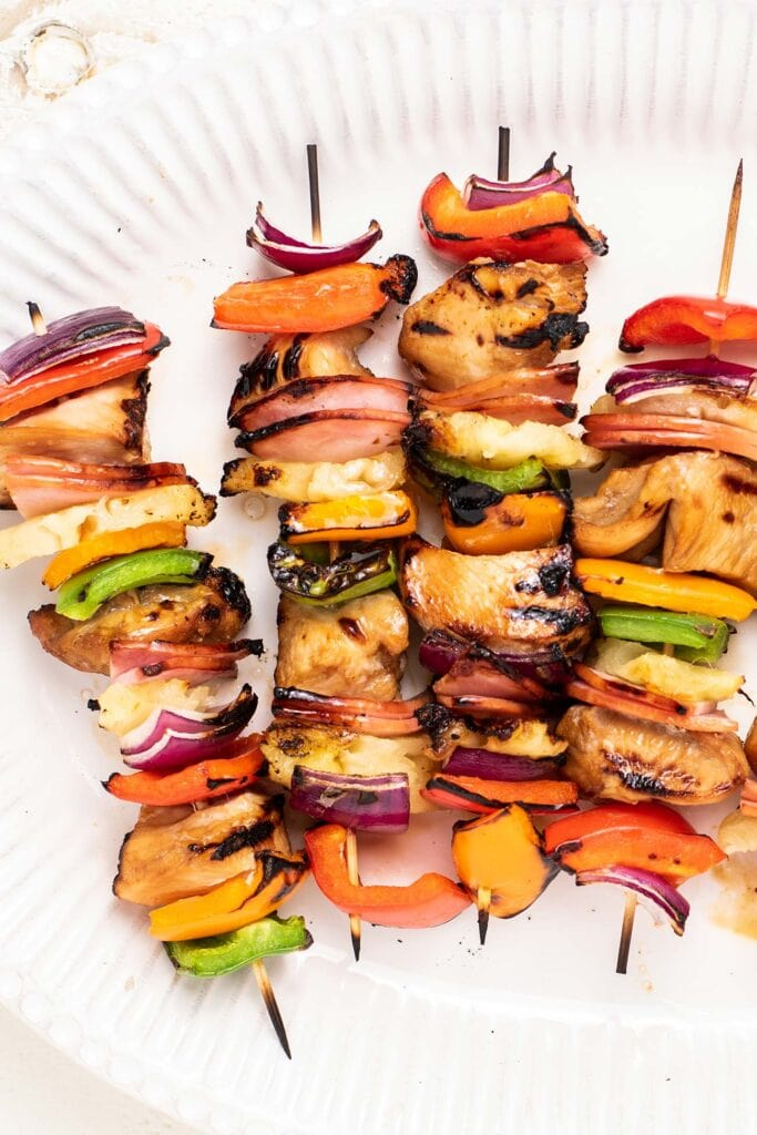 A close up look at 4 chicken skewers with purple onion and colorful bell peppers.