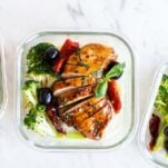 Balsamic vinegar chicken breasts shown sliced and packed with broccoli in meal prep boxes.