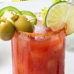 A tomato juice cocktail shown garnished with olives, jalapeno, and celery.