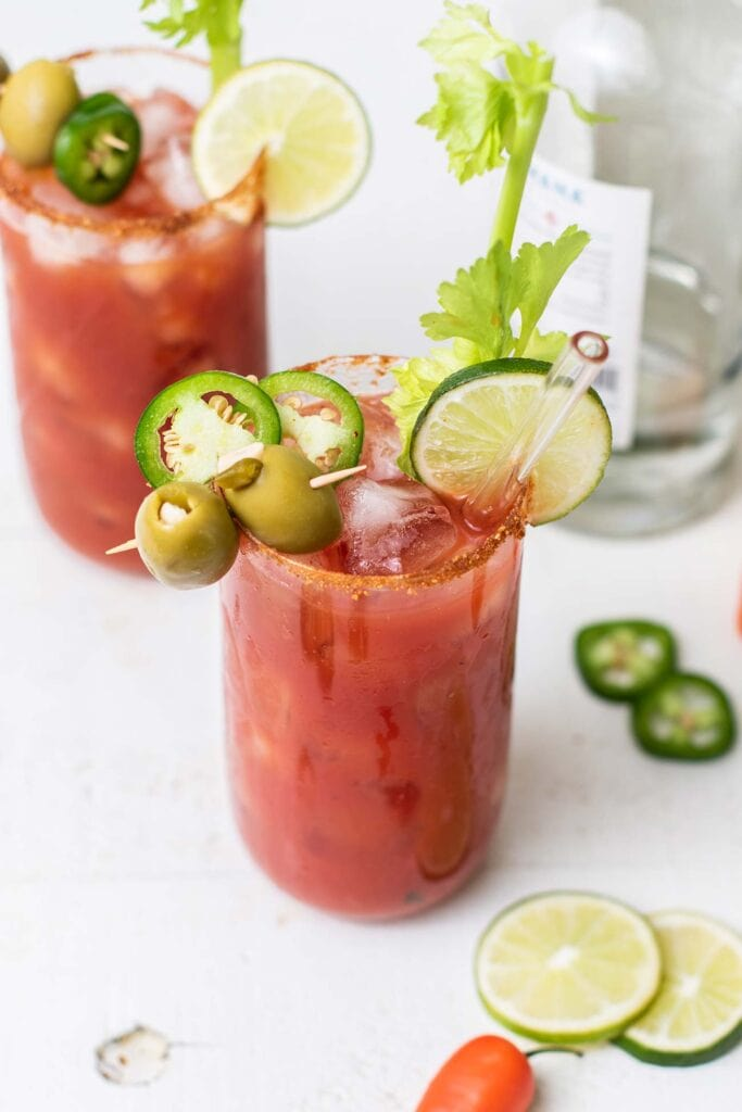 Two bloody maria cocktails garnished with celery, olives, and jalapeno.