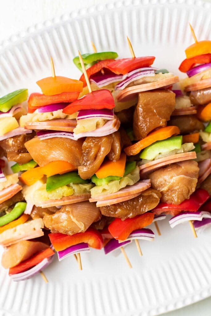 A plate of skewers prepared and ready to be grilled.