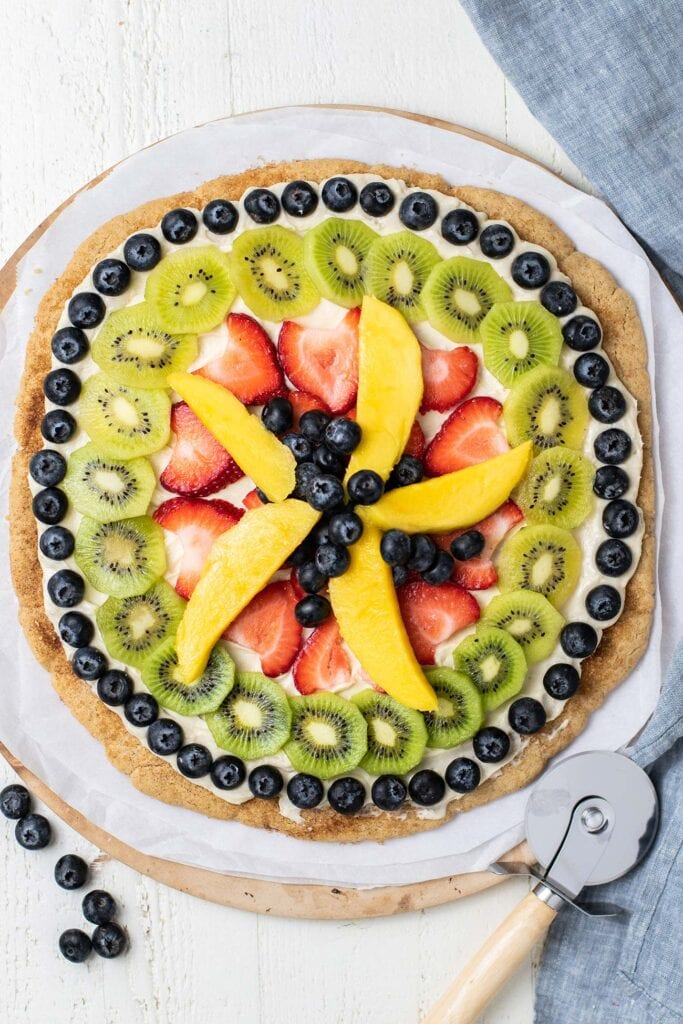 A fruit pizza shown with a pizza cutter.
