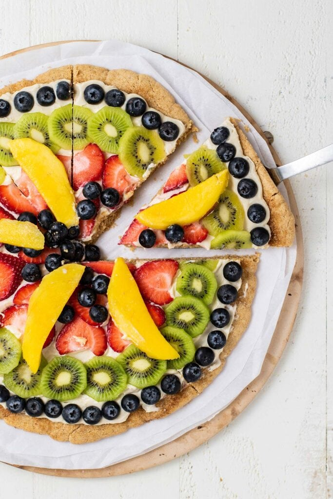A snickerdoodle fruit pizza shown cut into slices.