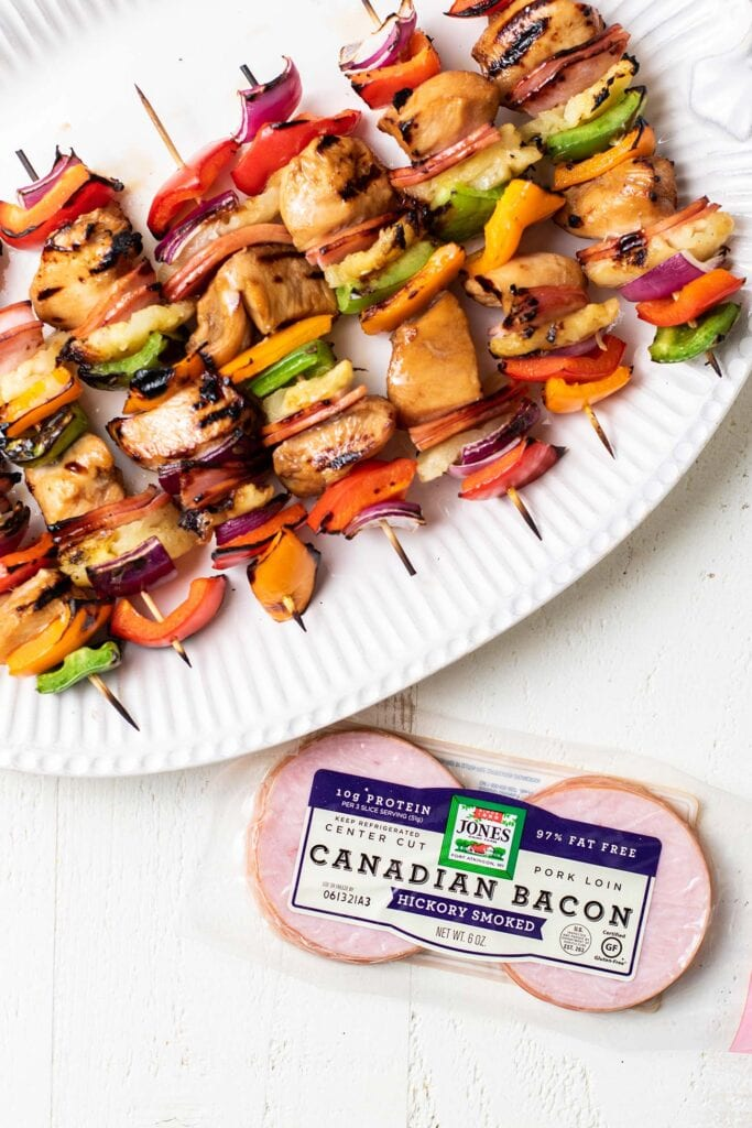 A platter of grilled teriyaki chicken skewers next to a package of Jones Dairy Farm Canadian Baon.