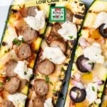 A close up look at zucchini pizza boats topped with sausage and veggies.