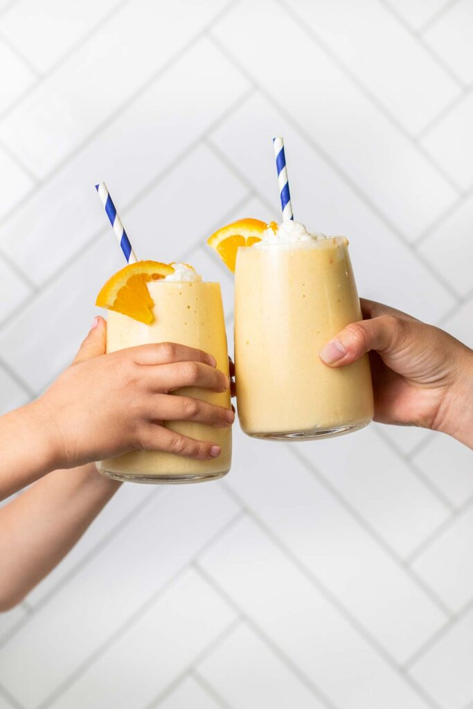 A child and an adult both holding an orange smoothie to cheers.
