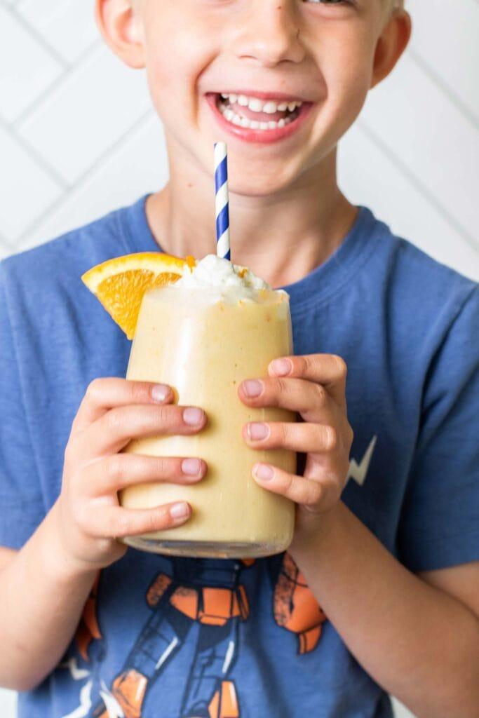 A happy kid holding an orange julius smoothie.