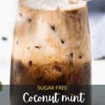 A coconut milk iced mocha with peppermint shown in a glass with mint leaves and coffee beans.