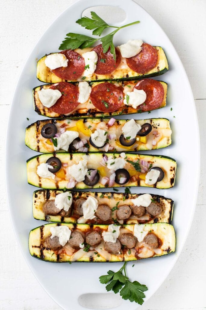 A plate with 6 zucchini pizza boats shown topped with pepperoni, veggies, and sausage.