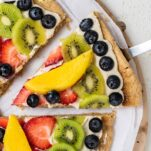 A close up of a slice of fruit pizza being picked up with a spatula.