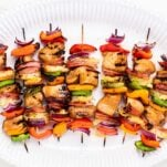 A white platter with colorful grilled teriyaki chicken skewers.