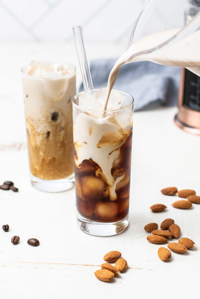 A pitcher pouring almond milk creamer into a glass of iced coffee.